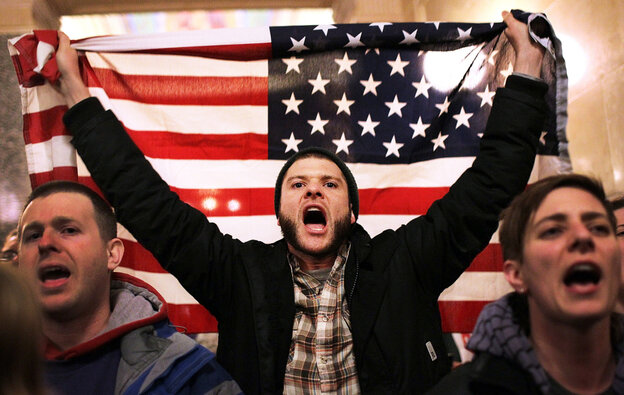 For so many reasons, Americans are seething. Here, a protester shouts as he holds an American flag after storming the Wisconsin state Capitol in Madison last March, after Republicans in the state Senate voted to curb collective bargaining rights for public workers.