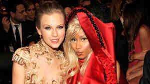 The improbable pair of country star Taylor Swift and rapper Nicki Minaj sitting together at the Staples Center Sunday night.