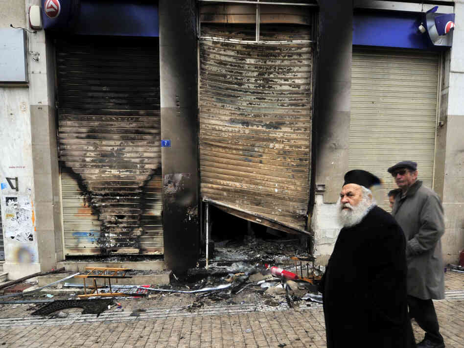A Greek priest walks past a burned bra