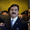 Pakistani Prime Minister Yousuf Raza Gilani is surrounded by security personnel as he arrives at Supreme Court for a hearing in Islamabad, Pakistan on Monday.