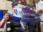 Supporters of Rick Santorum and Mitt Romney vie for attention at CPAC in Washington, Saturday, Feb. 11, 2012.