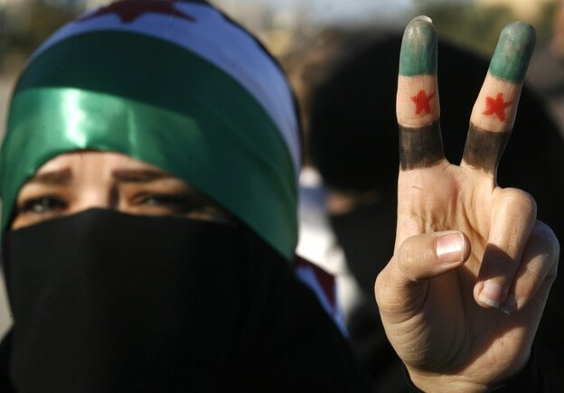 A woman flashes the V for 'victory' sign with her fingers painted in the colors of the former Syrian flag during a protest against the Syrian regime outside Damascus' embassy in Kuwait City on Feb. 5, 2012.