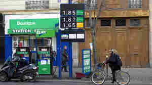 Gas prices in France have topped more than $8 a gallon in some areas. In this photo from January, a woman rides her bike past a gas station in Paris.