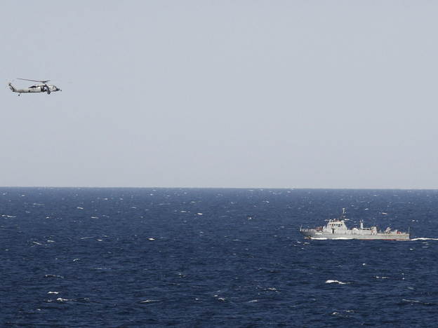 A helicopter from the aircraft carrier USS Abraham Lincoln hovers over an Iranian patrol ship during a transit through the Strait of Hormuz on Tuesday.