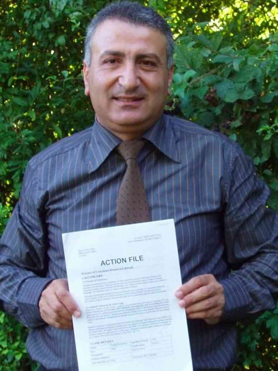 "Syrian activist Dr. Kamal Labwani poses in this file photo from 2005, holding an ""action file"" compiled by Amnesty International about his case."