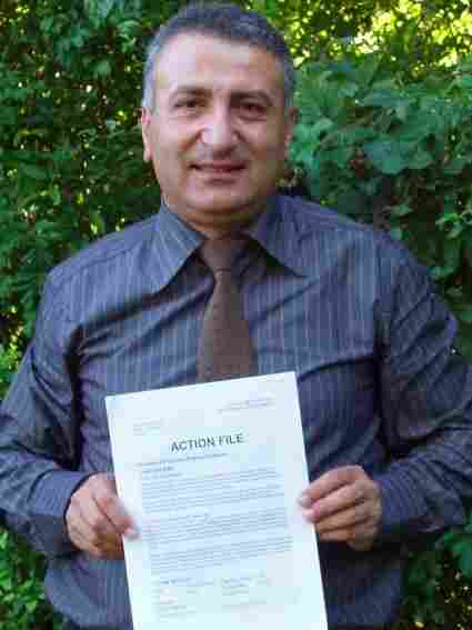 """Syrian activist Dr. Kamal Labwani poses in this file photo from 2005, holding an """"action file"""" compiled by Amnesty International about his case."""