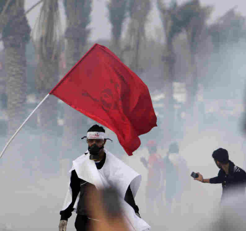 Bahraini anti-government protesters react to tear gas fired by riot police on Monday.