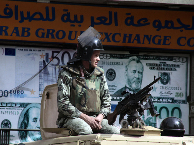 An Egyptian soldier on an armored vehicle guards an exchange office in Cairo on Monday. Tensions between the U.S. and Egypt are rising over Cairo's investigation of aid workers, many of them American. An Egyptian Cabinet minister, Faiza Aboul Naga, recently accused the U.S. of directly funding pro-democracy groups in order to create chaos in Egypt.