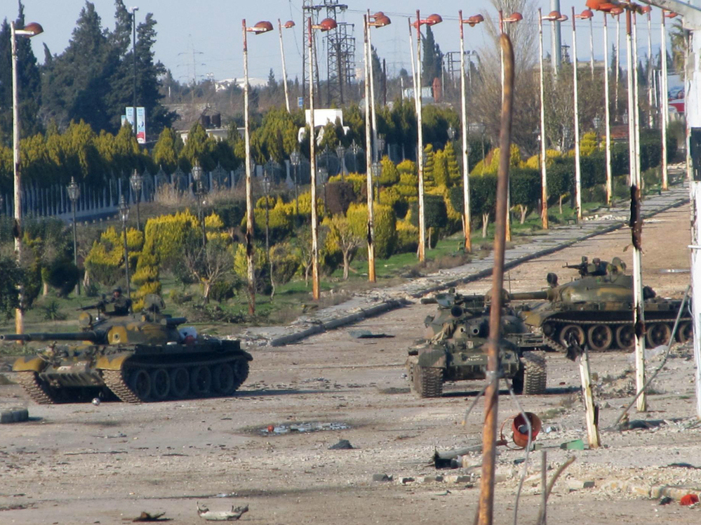 Syrian army tanks are seen stationed at the entrance to Baba Amr neighbourhood in Homs on Feb. 13, 2012. Syria ignored a new Arab initiative to end the bloodshed, with its troops pounding the protest hub of Homs as Russia said a ceasefire is needed before peacekeepers can be deployed.