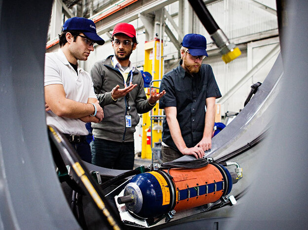 From left, enginers Eric Nicosia, Amin Ahmadi and Gavin Boogs work to solve an issue with part of a wind turbine at the Gamesa Corp. factory in Langhorne, Pa., on Feb. 10.