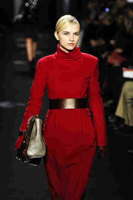 A model shows off a cherry red coat with a funnel neck and wide belt at the Diane von Furstenberg show.