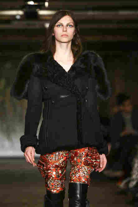 "Another designer returning to simpler ground is Joseph Altuzarra, whose parkas were a great success last year. ""All the conceptual pieces that he had done before didn't matter as much as a staple item that a superfashionable girl could wear day in, day out on the street,"" Singer says. This year, he returns with a black shearling coat with luxe fur trim and a thin leather belt. (Neilson Barnard/..."