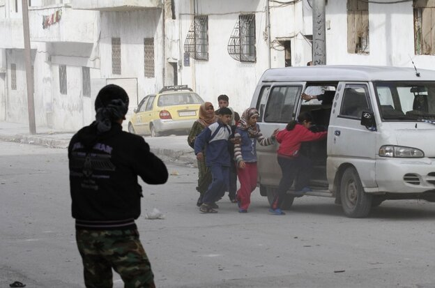 Civilians flee from fighting on Tuesday, after Syrian army tanks enter the northwestern city of Idlib, Syria.