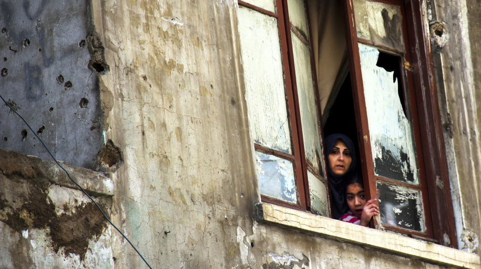 The fighting in Syria was seen as a spark for clashes in the Lebanese city of Tripoli last week. Here a Lebanese woman and her daughter look out the window of their bullet-pocked home in Tripoli on Sunday, Feb. 12.   (Adel Karroum/EPA /Landov)