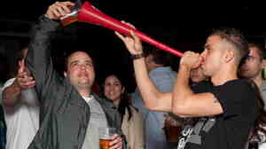 "Prime Minister David Cameron calls binge drinking ""one of the scandals of our society."" Here, a man drinks a pint of beer through a makeshift ""Vuvuzela of Ale"" in London, in a file photo from 2010."