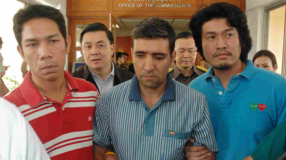 Thai immigration officers escort detained Iranian Mohammad Kharzei, center, at the immigration headquarters in Bangkok on Thursday.