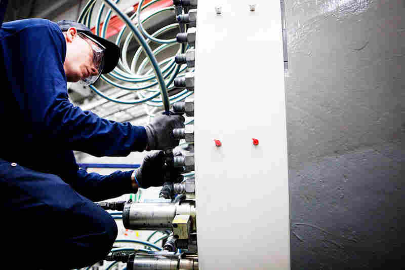 Joseph Wright tightens bolts on the hub of a wind turbine. Sixty percent of the components used in wind turbines are manufactured in the U.S., according to the American Wind Energy Association.