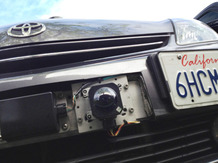 A car camera attached to the front bumper of Google's driverless car.