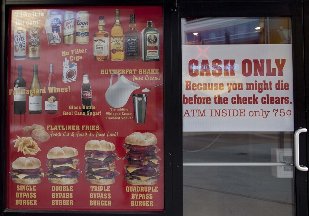 "Signs for ""Bypass Burgers"" and ""Flatliner Fries"" are seen in the window of the Heart Attack Grill in Las Vegas. A man who suffered a heart attack in the restaurant was wheeled out on a stretcher Saturday."