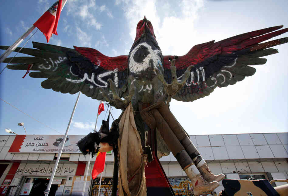 "A falcon statue, painted in the colors of the revolutionary flag and covered with the inscription ""God is great"", and is displayed outside the museum set up on Tripoli boulevard in Misrata on Feb. 12."