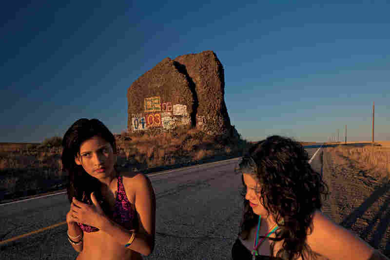 Brenda Diaz and Jessica Ruiz take a break near Yeager Rock during a road trip. Native Americans used to mark boulders with carvings. Today's artists, some of whom have immortalized the years of their high school graduations here, prefer paint.