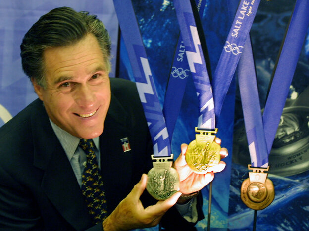 Mitt Romney, then-president of the Salt Lake Organizing Committee, displays medals that would be awarded at the 2002 Winter Olympics in October 2001.