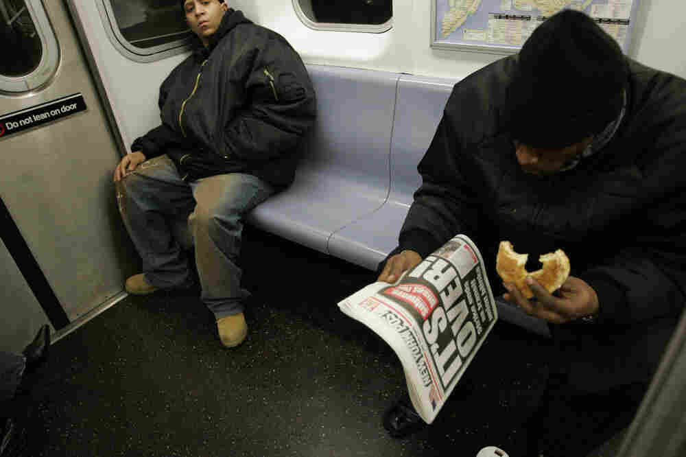 A man commutes to work on the New York City subway while enjoying breakfast in 2005. A New York state senator has proposed a law that would ban eating on the subway, in hopes of driving away rats.