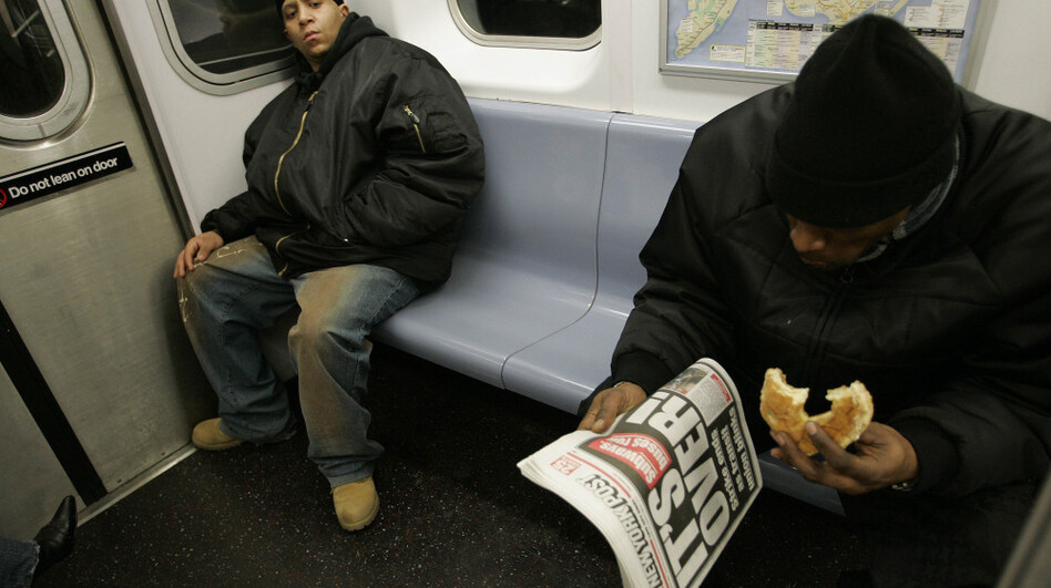 A man commutes to work on the New York City subway while enjoying breakfast in 2005. A New York state senator has proposed a law that would ban eating on the subway, in hopes of driving away rats.  (AP)