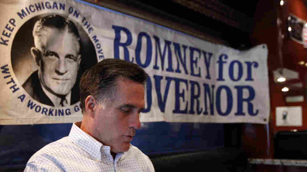 Mitt Romney works Thursday in Michigan aboard his campaign bus, which displays a poster for his late father, former Michigan Gov. George Romney. Despite deep roots in the state, Romney finds himself battling a candidate who has barely visited.