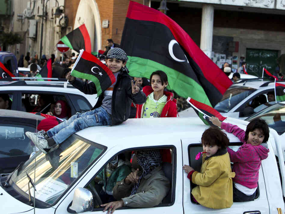 Children in Tripoli, Libya, wave a