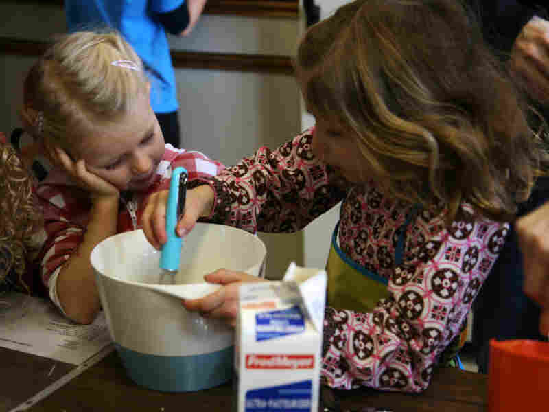Clara Peterson, 5, and Pia Patrikson, 6, take turns whipping cream by hand.