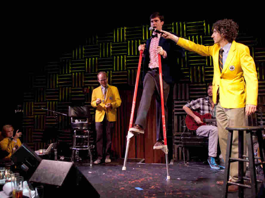 "Dan Rollman, the co-founder of RecordSetter, holds up a microphone to Rob Lathan, who currently holds the world record for completing 81 leg kicks on stilts while singing ""New York, New York,"" at a World Record Appreciation Society event in New York City."