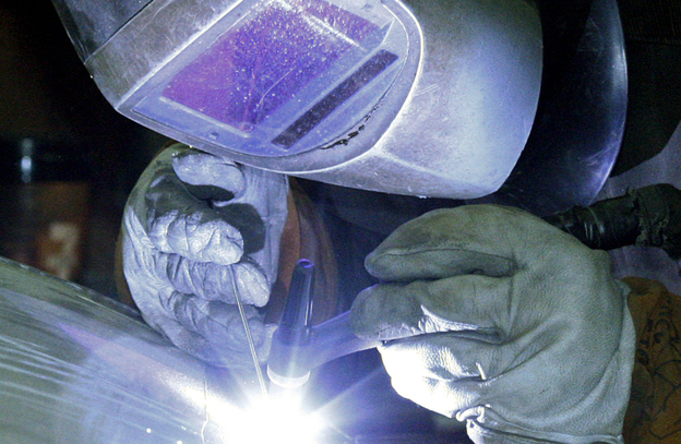 An employee welds a stainless steel tank at JV Northwest in Camby, Ore. U.S. factories have boosted output, and busier factories are helping drive the U.S. economy.