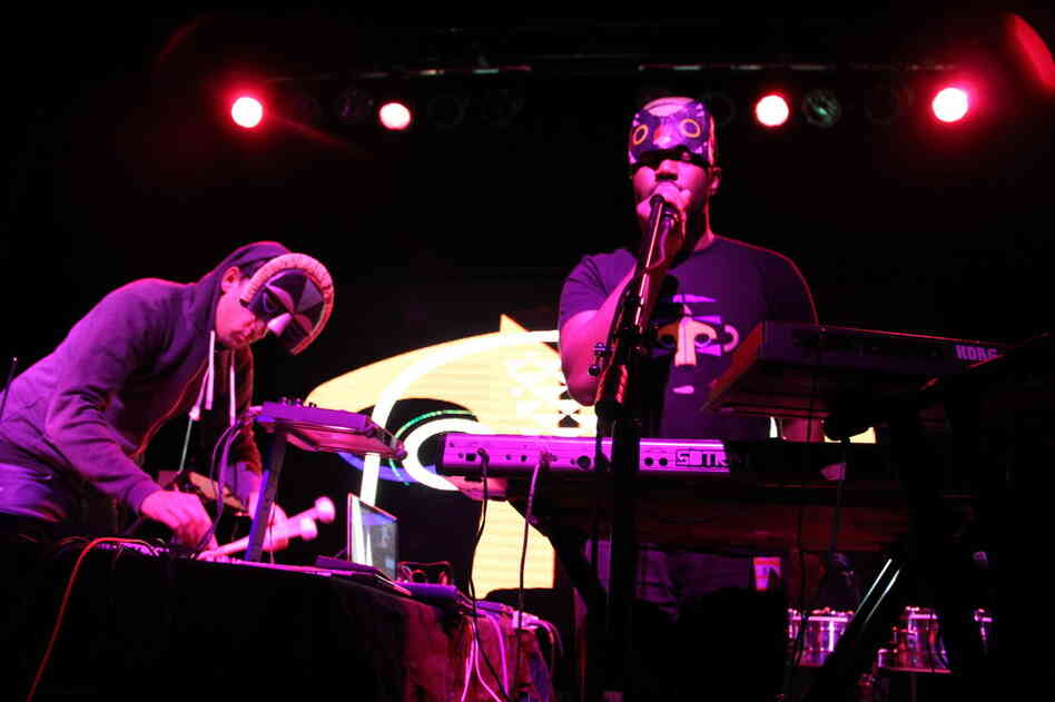 The singer Sampha (at right, in mask T-shirt) performs with SBTRKT in concert. During performances, the producer wears a mask that covers just half of his face.