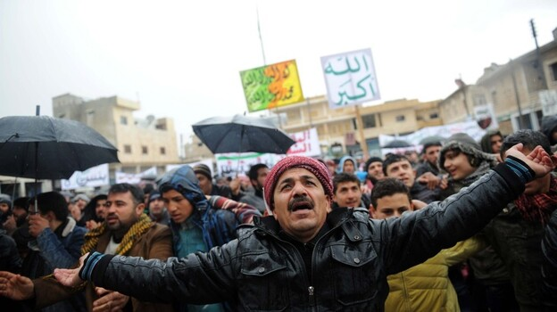 Syrians demonstrate against the regime after Friday prayers in the north Syrian city of Idlib on Friday. Thousands of Syrians rallied to demand Bashar al-Assad's ouster, as the embattled president's forces unleashed their heaviest pounding yet of Homs in a brutal bid to crush dissent, monitors said.  (AFP/Getty Images)