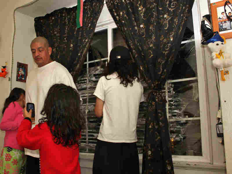 Pedro Jimenez and three of his kids, in the living room of their Oakland, Calif., apartment. JPMorgan Chase hasn't hired a management company to fix the shattered window panes or make other repairs.