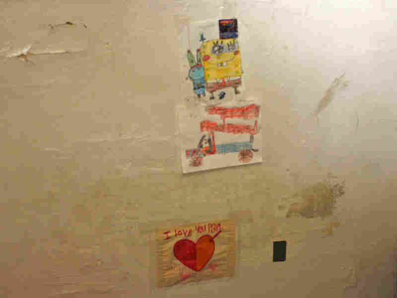 "David Jimenez, 7, patches up holes in his East Oakland, Calif., apartment. The bottom sticky note says, ""I love you Papi."""