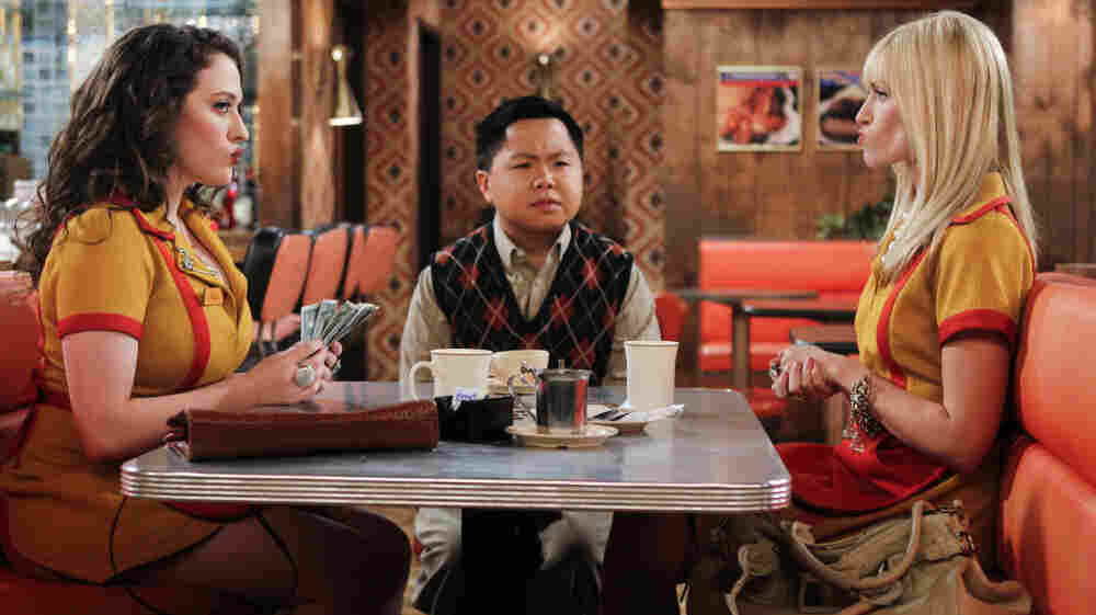 Han Lee (Matthew Moy), owner of the Brooklyn diner where Max (Kat Dennings, left) and Caroline (Beth Behrs, right) work, joins the two women as they count their earnings on 2 Broke Girls.