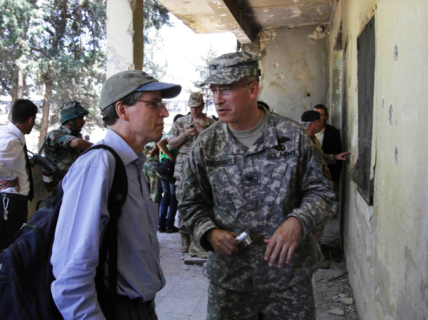 Robert Ford (left), the U.S. ambassador to Syria, speaks to an unidentified U.S. military attache during a guided government tour in the northern Syrian town of Jisr al-Shughur last June. The U.S. has closed its embassy in Syria owing to security concerns, but Ford is using Facebook to stay involved in the country.