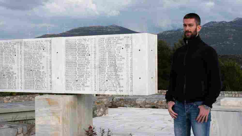 Nikos Bouras, 37, stands next to a monument for those massacred by the Nazis on June 10, 1944, that stands atop the highest hill in the Greek town of Distomo.
