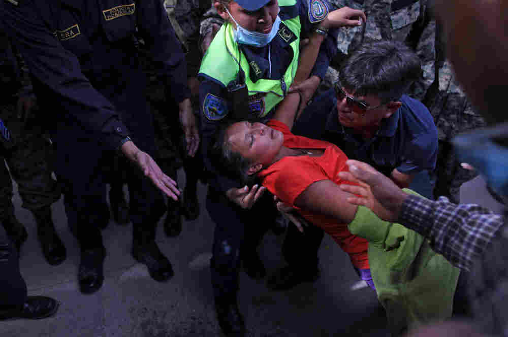 A woman is taken away by police after fainting during clashes when relatives of inmates killed during last week's prison fire stormed the restricted area of the morgue in Tegucigalpa, Honduras on Monday.