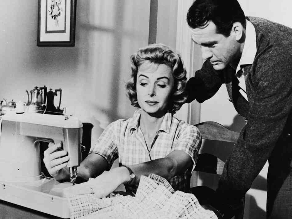 American actress Donna Reed sews on sewing machine as American actor Carl Betz watches over he
