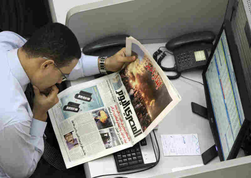 An Egyptian stock trader reads a copy of the Al-Masry Al-Youm newspaper last November. Critics say the newspaper is reluctant to criticize the ruling military council and has engaged in self-censorship.