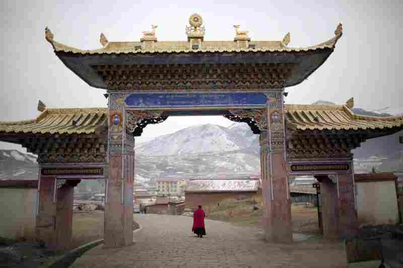 A monk walks under a temple entrance during Tibetan New Year celebrations in Langmusixiang, in China's western Sichuan Province Feb. 22, 2012.