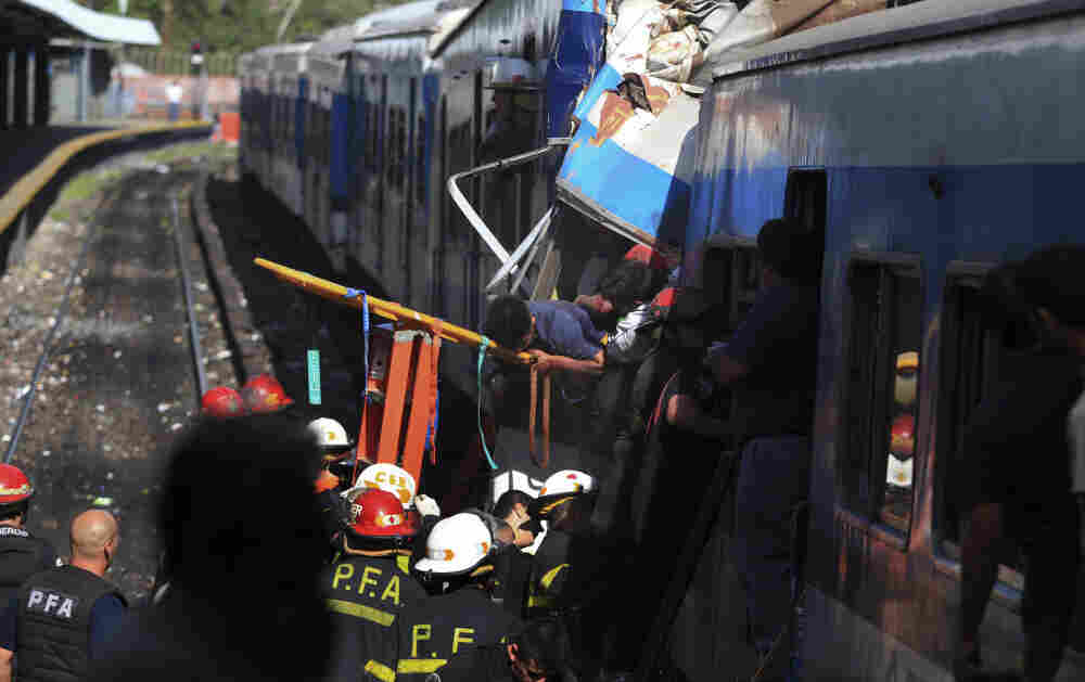 Firemen rescue wounded passengers from a commuter train after it crashed in Buenos Aires, Argentina, Wednesday Feb. 22, 2012.