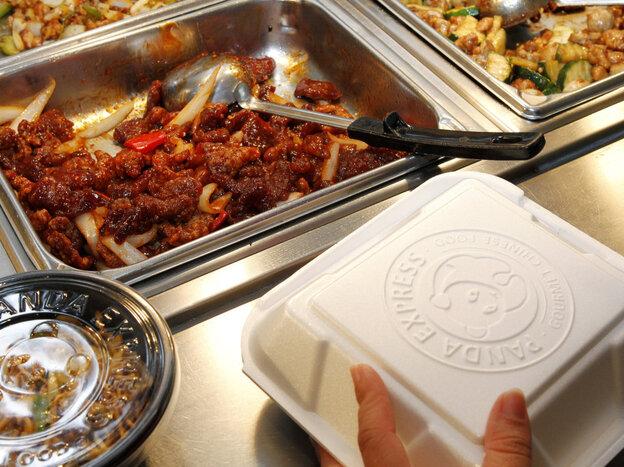 An employee packs a customer's takeout order at a Panda Express restaura