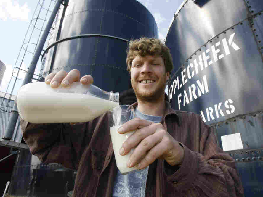 John Clark pours raw milk into a glass at Applecheek Farm in Hyde Park, Vt.