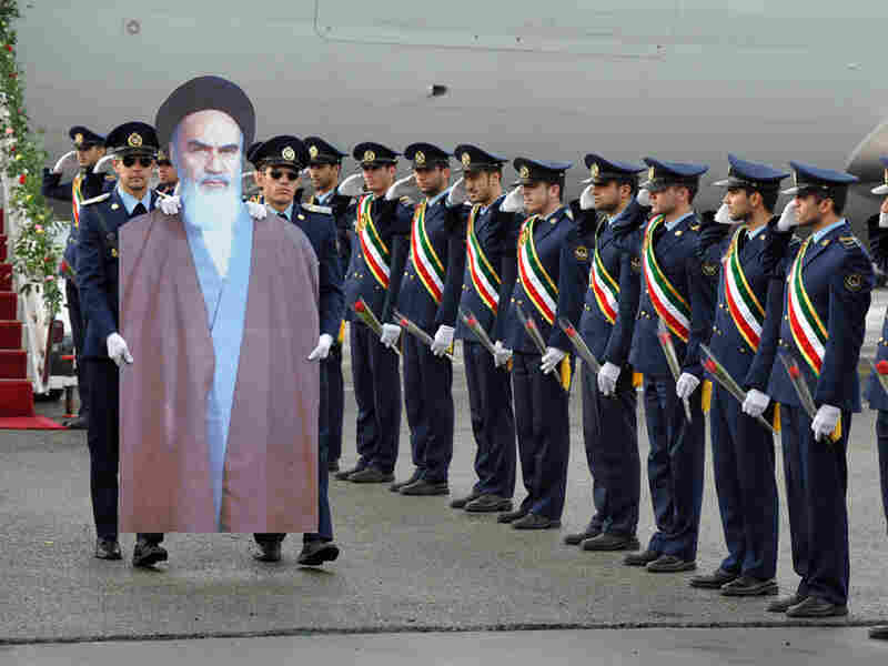 Iranian air force soldiers carry a cardboard cut out of the late founder of the Islamic Republic, Ayatollah Khomeini, from a passenger plane at Merhrabad airport on Feb. 1, 2012 during a ceremony to re-enact his arrival to Tehran in 1979.