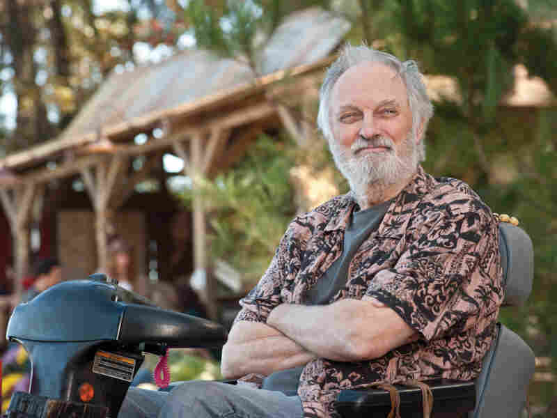 Alan Alda plays Carvin, the founder of the commune, a rural intentional community called Elysium.