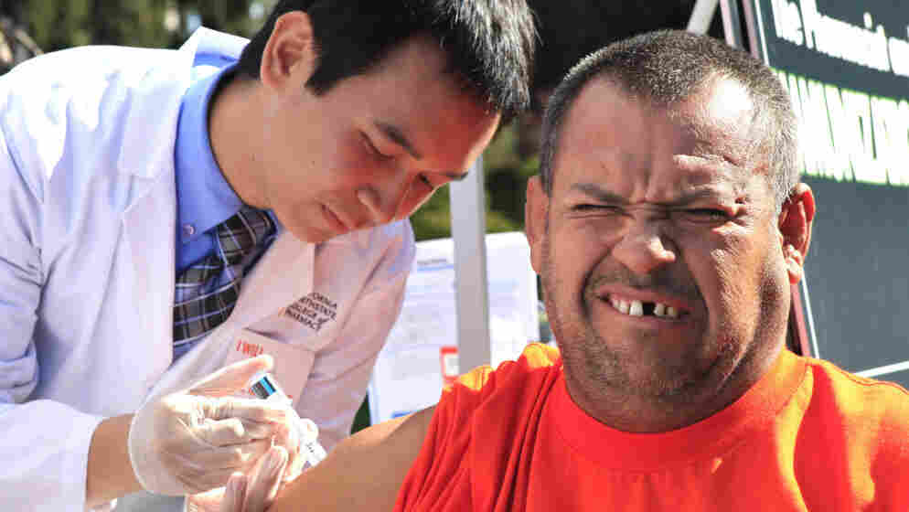 Ramon Maldonado-Cardenas grimaces as he gets a flu shot from pharmacy student Khoa Truong during a health fair in Sacramento, Calif., last October.